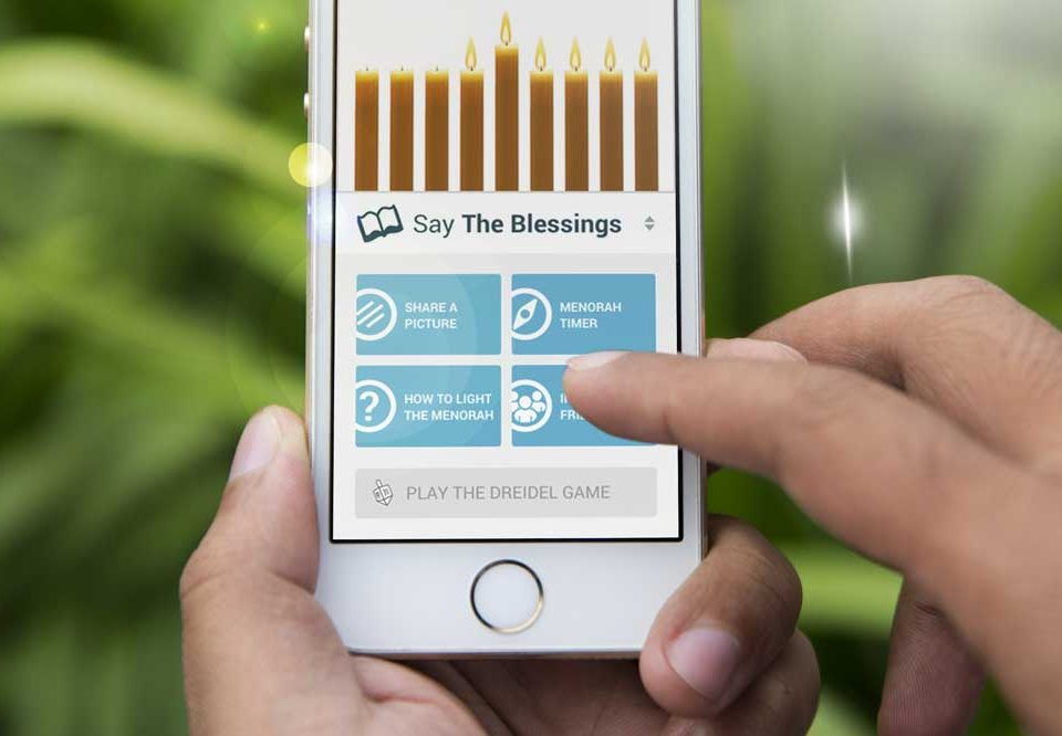 Jewish app user on iphone with Chanukah app